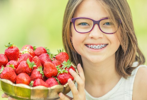 girl with metal braces holding strawberries