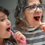child and mom brushing teeth