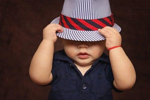 toddler hiding under hat
